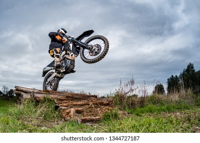 Enduro bike rider in action. Obstacle overcome on mud and grass terrain.