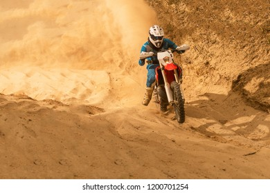 Enduro bike rider on action. Turn on sand terrain.