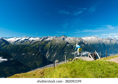 enduro bike rider starting on the high mountain technical trail in austrian alps on wildkogel im salzburg with glacier peaks view