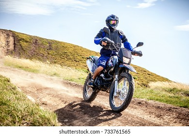 Enduro biker crossing road at high speed in Carpathian mountains. Ukraine.