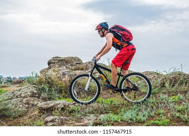Enduro Cyclist Riding the Mountain Bike on the Rocky Trail, copy of free space. Extreme Sport Concept.