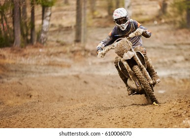 Enduro driver in action driving the motorbike on  the muddy race track.