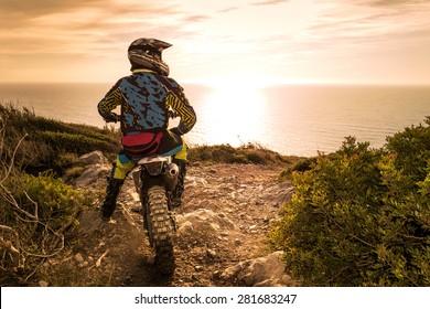 Enduro racer sitter på sin motorcykel tittar på solnedgången.