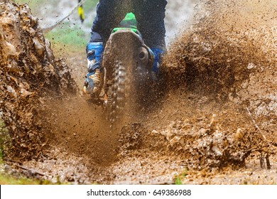 enduro rides through the mud with big splash,driver splashing mud on wet and muddy terrain,Motocross racer in a wet and muddy terrain covering the driver completely.