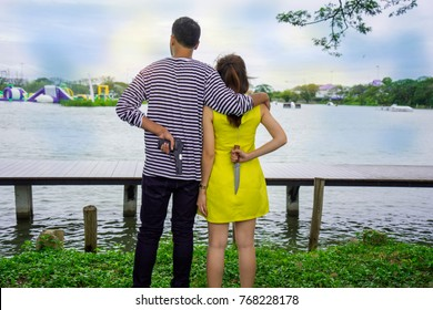 Enemy couple, unfaithful lover, affair family, cheating husband and wife, man holding woman shoulder looking forward but both hide holding gun and knife behind. Love hate relationship concept.