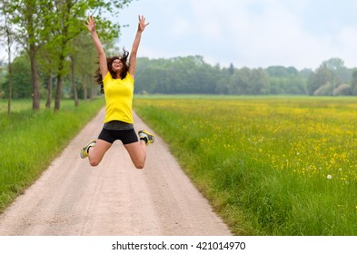 Energetic agile young woman leaping for joy jumping midair on a rural dirt road through lush green spring meadows as she rejoices in nature