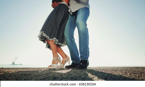 Energetic attractive young couple dancing latin Bachata near sea or ocean. Sunlight background. Summer time, romantic image