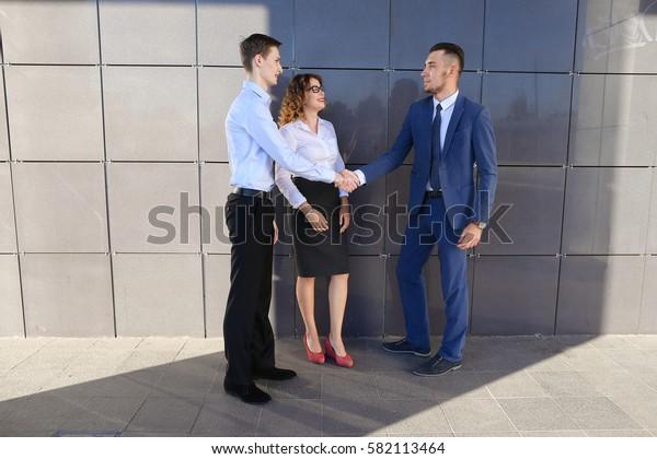 Energetic beautiful young guys and girl, businessmen and students to meet and discuss important issues, share business ideas, smiling, laughing, make decisions, solve problems and standing near gray