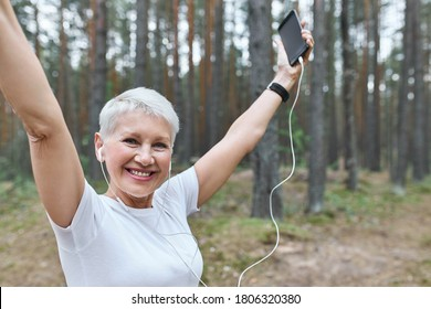 Energetic cheerful retired female with fit slim body posing outdoors in earphones, raising hands, holding cell phone, enjoying music tracks, running. Sports, achievement, goals and determination