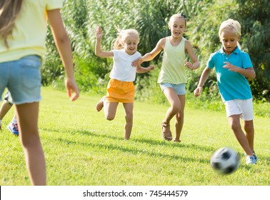 energetic children running with ball on meadow outdoors . Selective focus