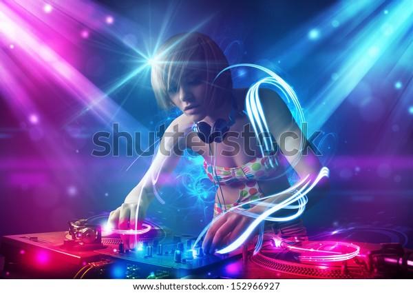 Energetisches Dj-Mädchen, das Musik mit kraftvollen Lichteffekten mischt