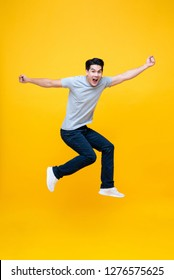 Energetic excited young Asian man in casual clothes jumping studio shot isolated in colorful yellow background