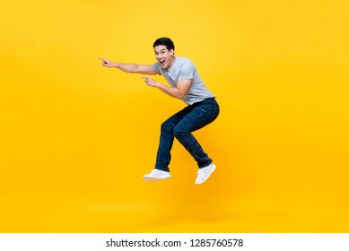 Energetic excited young Asian man jumping and pointing hand to empty space aside studio shot isolated on colorful yellow background