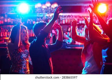 Energetic friends dancing in night club