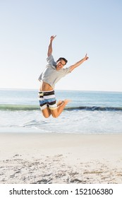 Energetic handsome man jumping on the beach