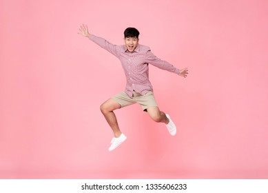 Energetic happy smiling young Asian man in casual clothes jumping studio shot isolated in colorful pink background