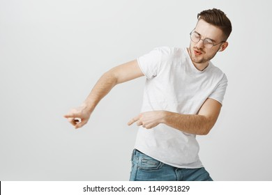 Energetic satisfied handsome young european male in casual white t-shirt dancing tilting right and making moves to rhythm of song listening music and enjoying great sound quality in wireless earphones