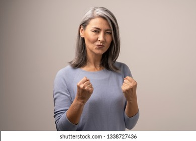 Energetic Senior Asian Woman Is Clenching Her Fists In Victory. Happy Woman Clenching Her Fists And Making A Duck Face. Portrait.