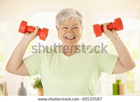 Energetic Senior Woman Doing Dumbbell Exercises Stock Photo (Edit