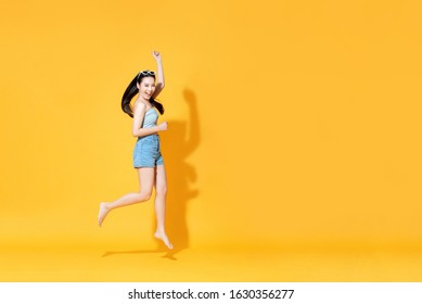 Energetic smiling beautiful Asian woman in summer outfit jumping isolated on yellow background