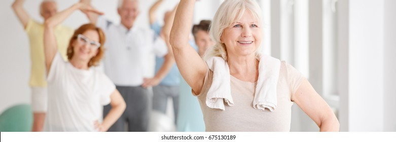Energetic smiling senior woman exercising with a group of elders
