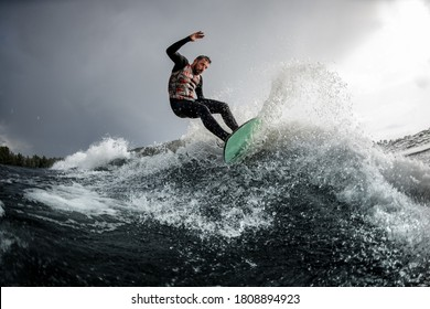 energetic sports man is surfing on surfboard trails behind boat. Wakesurfing on the river. Summertime leisure