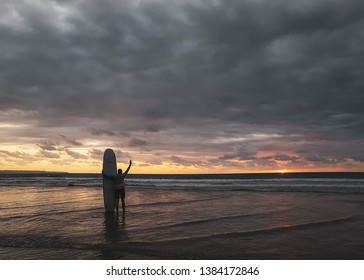 Energetic surfer with his surfboard waving at the ocean on a cloudy day during a beautiful sunset at Kuta beach, Indonesia