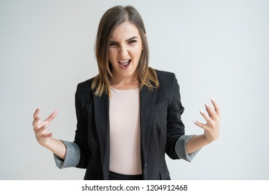 Energetic young Caucasian woman raising hands and screaming. Ready for fight pretty dark-haired manager gesturing and looking at camera. Business as warzone concept