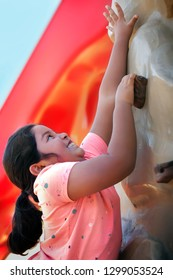 An energetic young girl extends her arm trying to reach the next grip on an outdoor rock climbing wall, with a big smile on her face.