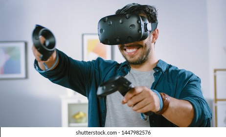 Energetic Young Man Wearing Virtual Reality Headset and Holding Controllers Plays in a Video Game at Home. Active Man Playing VR Quest Adventure Videogame in the Middle of Living Room.
