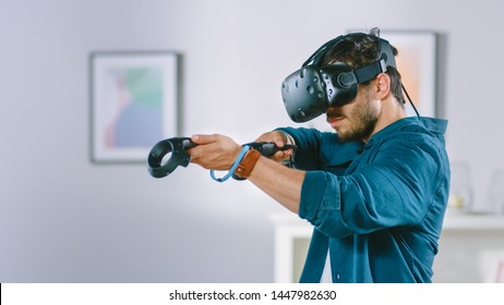 Energetic Young Man Wearing Virtual Reality Headset and Holding Controllers Plays in a Video Game at Home. Man Playing VR Shooter in the Middle of Living Room.