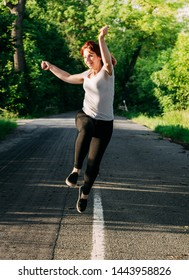 Energetic young woman running and leaping down a rural wooded road in summer smiling as she celebrates the sunshine