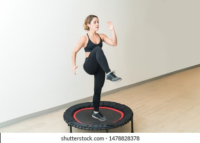 Energetic young woman in sportswear trampolining against white wall during high intensity interval training