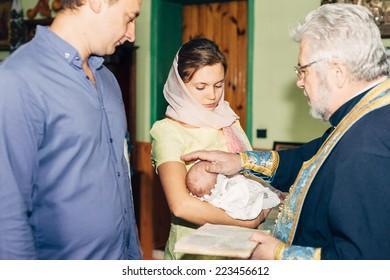 Energodar, UKRAINE - September 24, 2014: The Holy Orthodox rite of the sacrament of baptism newborn baby in a small Christian Church September 24, 2014 in Energodar, Ukraine.