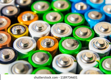 Energy abstract background of colorful batteries. Close-up group of alkaline battery top view. 