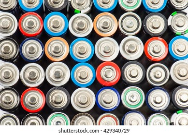 Energy abstract background of colorful batteries. Close up top view on rows of selection of AA batteries.