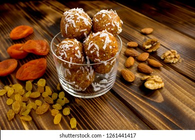 Energy balls with dried apricots and ingredients in the glass plate  on the brown wooden background