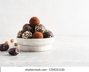 Energy balls. Healthy raw dessert (bliss balls), vegetarian truffles, sugar free candies made of dates, hazelnuts, cocoa powder. Step by step cooking. White wooden background.