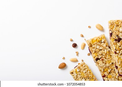 Energy bar of muesli with nuts, berries and oat flakes on a white background. Healthy food, granola for breakfast. Top view.