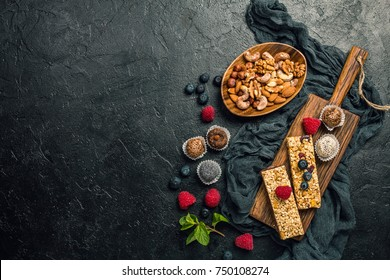Energy bars and balls - snack for healthy lifestyle on black background, top view