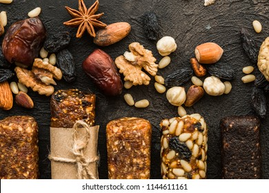energy bars with dried fruit, various nuts, stone background. Healthy vegan super food, different fitness diet snacks for sporty lifestyle. Top view, copy space.