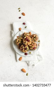 Energy bites with nuts, seeds, dry cranberries and honey - vegan vegetarian raw organic snack granola bites on white background, top view.