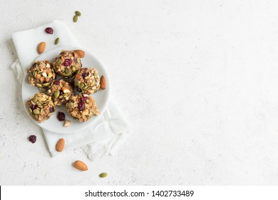 Energy bites with nuts, seeds, dry cranberries and honey - vegan vegetarian raw organic snack granola bites on white background, copy space.