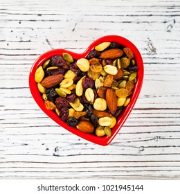 Energy Blend Trail Mix with Nuts and Dried Fruits in Heart Shaped Bowl. Selective focus.