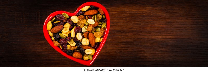 Energy Blend Trail Mix with Nuts and Dried Fruits in Heart Shaped Bowl. Panoramic image. Selective focus.