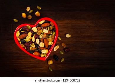 Energy Blend Trail Mix with Nuts and Dried Fruits in Heart Shaped Bowl on Wooden Background. Selective focus.
