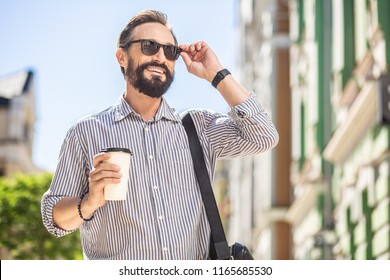 Energy booster. Cheerful stylish man drinking coffee while walking in the street