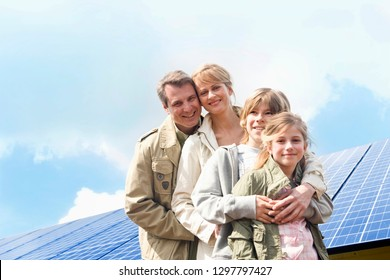 Energy concept with family standing with solar panels at camera
