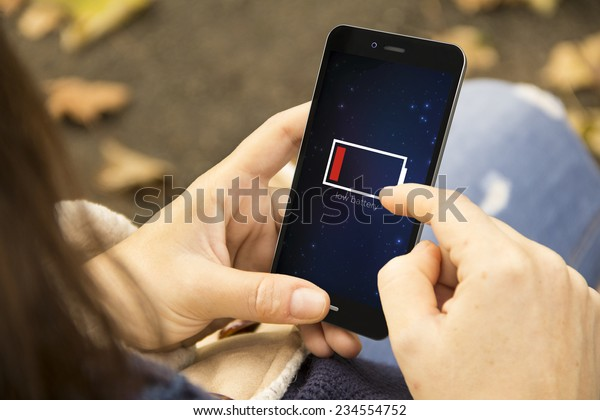 energy concept: Female hands using smart phone with low battery