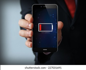 energy concept: Male hand holding a low battery mobile phone